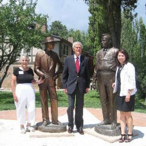 Nancy Bartlit, far left, with the bronze statues of Dr. Oppenheimer and General Leslie Groves.